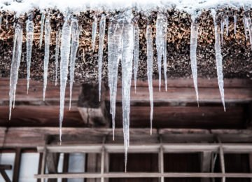 When it's freezing outside, a ridge of ice can form at the edge of the roof. It keeps water from draining. The water backs up instead.